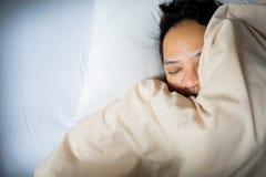 Slut upp av en asiatisk manframsida som sover på vit säng, bästa sikt royaltyfria foton