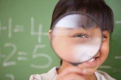 Slut upp av en gullig schoolgirl som ser till och med ett förstoringsglas Arkivfoto