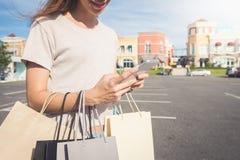 Slut upp av en håll för ung kvinna påsar för en shopping i henne hand och prata på hennes telefon, når att ha shoppat Royaltyfri Fotografi