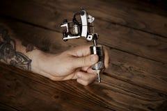 Slut upp av en hand för man` s med tatueringvapnet Arkivfoto