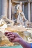 Slut upp av en hand för man` som s rymmer ett mynt främst av Springbrunn Di Trevi i Rome, Italien arkivbilder