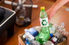 Slut upp av en hand som sätter en plast- flaska med ett utskrivavet tecken av återanvändning framme, inom av en kartong mycket av Fotografering för Bildbyråer