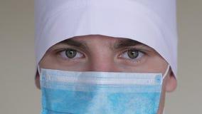 Slut upp av en iklädd manlig framsida för kirurg` s en kirurgisk maskering som ser kameran stock video