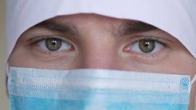 Slut upp av en iklädd manlig framsida för kirurg` s en kirurgisk maskering som ser kameran arkivfilmer
