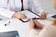 Slut upp av en kvinnlig doktorspåfyllning en ansökningsblankett, medan konsultera patienten fotografering för bildbyråer