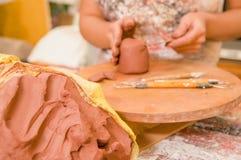 Slut upp av en leramass med en suddig kvinnaceramist bak att arbeta på skulptur på trätabellen i seminarium, i a arkivbilder