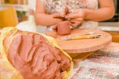 Slut upp av en leramass med en suddig kvinnaceramist bak att arbeta på skulptur på trätabellen i seminarium, i a royaltyfri fotografi