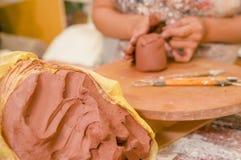 Slut upp av en leramass med en suddig kvinnaceramist bak att arbeta på skulptur på trätabellen i seminarium, i a royaltyfri bild