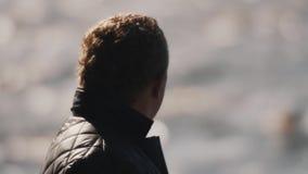Slut upp av en man i den svarta västen som ser sjövatten oskarp bakgrund stock video