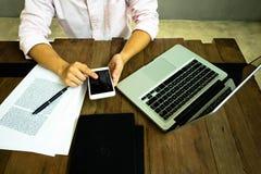 Slut upp av en man som använder den smarta telefonen för mobil på tabellen royaltyfria bilder