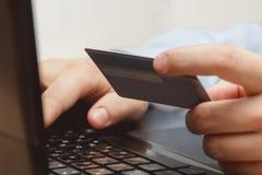 Slut upp av en man som shoppar direktanslutet genom att använda bärbara datorn med kreditkorten Arkivbild