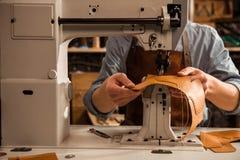 Slut upp av en skomakare som använder symaskinen fotografering för bildbyråer