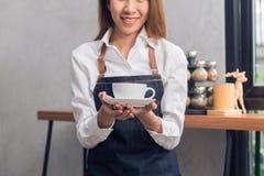 Slut upp av en ung asiatisk kvinnlig baristahåll per koppen kaffe som tjänar som till hennes kund med leende som omges med stångr Royaltyfria Foton