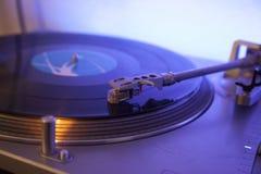 Slut upp av en visare som spelar ett vinilorekord som isoleras på ett blått lett ljus Arkivbilder