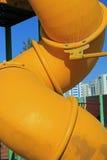 Slut upp av en vriden gul rörglidbana Arkivbild