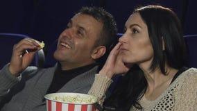 Slut upp av ett moget par som tillsammans håller ögonen på en film på bion royaltyfria foton