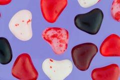 Slut upp av färgrika Valentine Candies på lilor Royaltyfri Bild