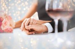 Slut upp av förlovade parinnehavhänder arkivfoton