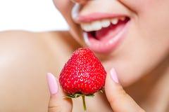 Slut upp av flickmunnen som äter jordgubben arkivbild
