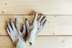 Slut upp av funktionsdugliga handskar mot trä royaltyfria bilder