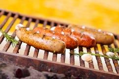 Slut upp av fyra grilla korvar på grillfestgaller med någon art BBQ i trädgården Bayerska korvar royaltyfri foto