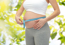 Slut upp av gravida kvinnan som mäter hennes mage Royaltyfri Fotografi