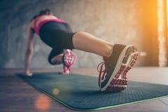 Slut upp av gymnastikskor för idrottskvinna` s Hon utbildar i solig roo Royaltyfri Foto