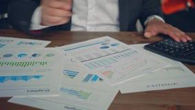 Slut upp av händer för en affärsman med pennan som arbetar på kontorsskrivbordet och analyserar grafer och diagram och skriver en arkivfilmer