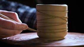 Slut upp av händer som arbetar lera på hjulet för keramiker` s Keramikern formar leraprodukten med krukmakerihjälpmedel på kerami arkivfilmer