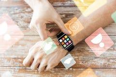 Slut upp av händer som ställer in den smarta klockan med symboler Royaltyfri Fotografi