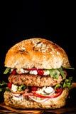 Slut upp av hamburgaren som högt travas med nya toppningar Arkivbild