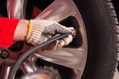 Slut upp av handen för mekaniker` som s kontrollerar lufttrycket av ett däck arkivfoto