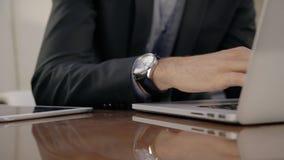 Slut upp av handen för sakkunnig analytiker för aktieägare den manliga med armbandsuret som arbetar på bärbara datorn stock video