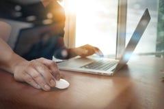 Slut upp av handen för affärsman som arbetar på bärbar datordatoren på trä Royaltyfri Foto