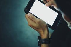 Slut upp av handen av mannen som använder smarta telefoner för mobil i mörkret Royaltyfri Foto
