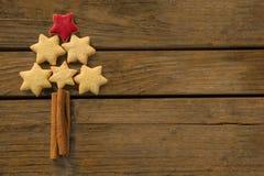 Slut upp av julgranen som göras med stjärnaformkakor och kanelbruna pinnar arkivfoton
