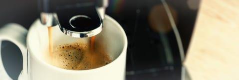 Slut upp av kaffebryggaremaskinen som häller bryggad varm espresso Fotografering för Bildbyråer