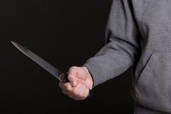 Slut upp av kniven i den manliga handen över grå färger Royaltyfri Foto