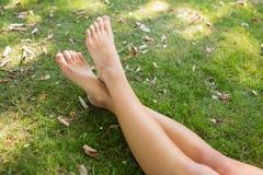 Slut upp av korsade ben av en kvinna som ligger på gräset Royaltyfria Bilder