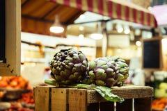Slut upp av kronärtskockor för ny grönsak i italiensk bondemarknad Royaltyfri Bild