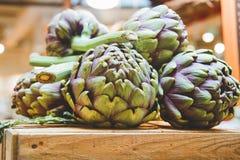 Slut upp av kronärtskockor för ny grönsak i italiensk bondemarknad Arkivbild