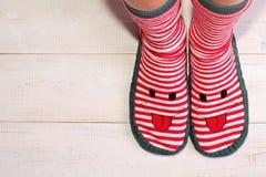 Slut upp av kvinnafot som bär roliga sockor med med den lyckliga smileyframsidan Det nya året och jul tid, är alltid och stagreal Royaltyfria Bilder