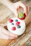 Slut upp av kvinnahänder med yoghurt och bär Arkivfoton
