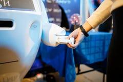 Slut upp av kvinnan som skakar händer med en robot royaltyfria foton