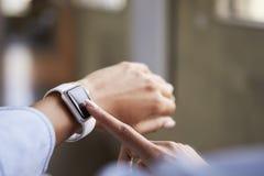 Slut upp av kvinnas händer genom att använda smartwatch arkivbild