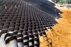 Slut upp av lutningserosionkontroll med raster och jord på stup Arkivbild