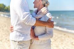 Slut upp av lyckliga höga par som kramar på stranden arkivbild