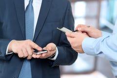 Slut upp av män för en affär som använder smarta telefoner för mobil Arkivbilder