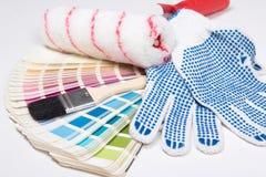 Slut upp av målares hjälpmedel - borstar, arbetshandskar och färgrikt Fotografering för Bildbyråer
