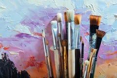 Slut upp av målningborstar och färgrik kanfas Arkivfoto